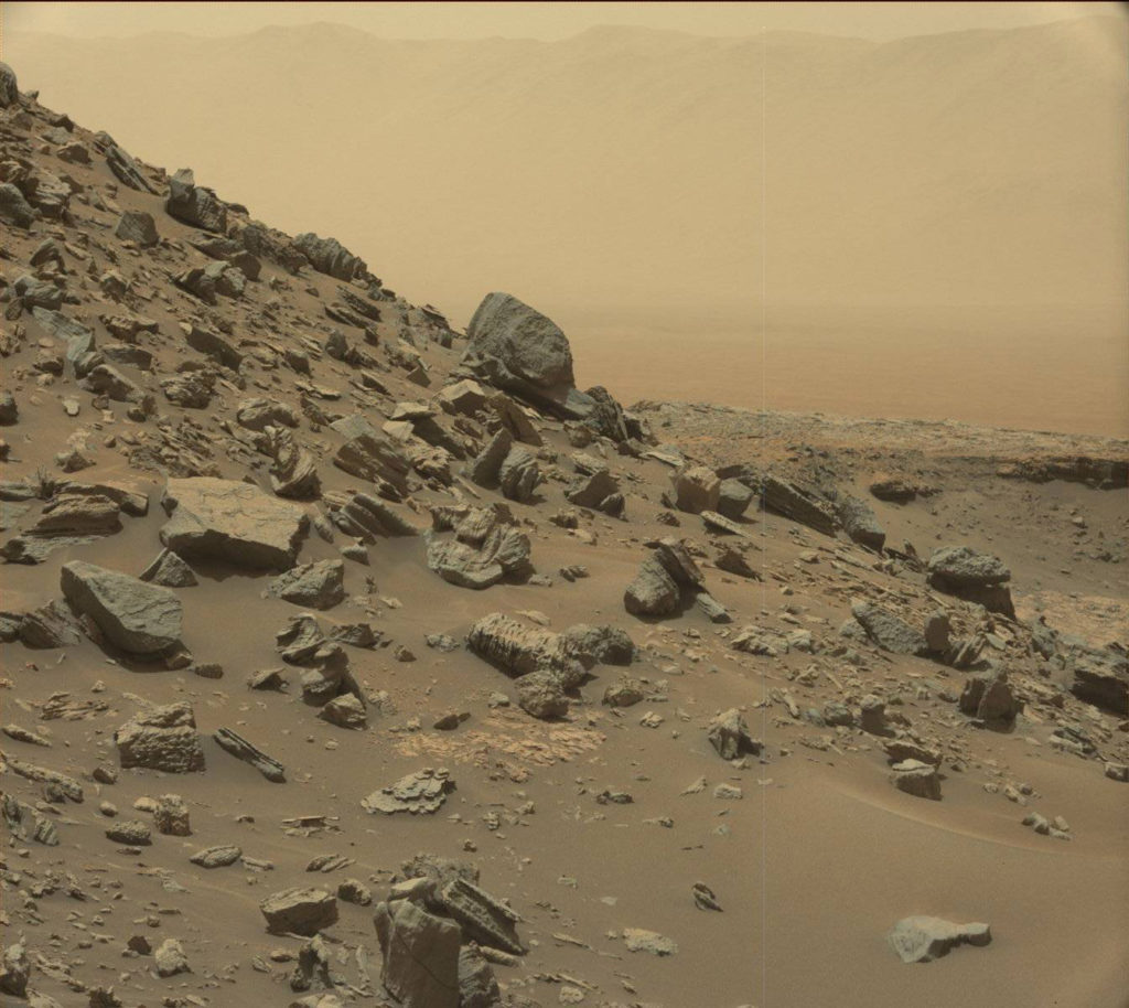 "This view from the Mast Camera (Mastcam) in NASA's Curiosity Mars rover shows a sloping hillside within the ""Murray Buttes"" region on lower Mount Sharp. The rim of Gale Crater, where the rover has been active since landing in 2012, is visible in the distance, through the dusty haze. The image was taken on Sept. 8, 2016, during the 1454th Martian day, or sol, of Curiosity's work on Mars. Image credit: NASA/JPL-Caltech/MSSS"