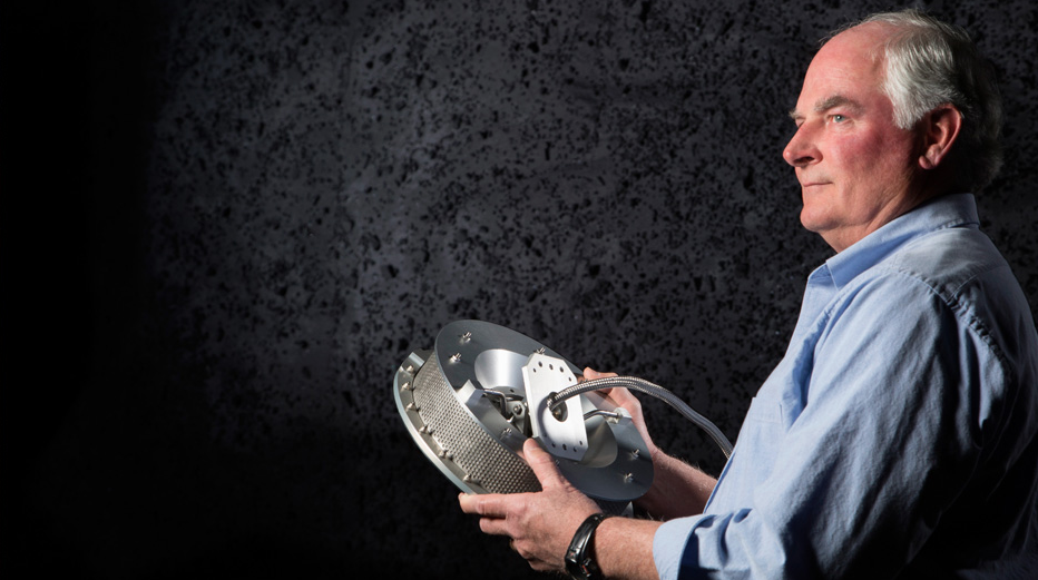 Engineer Jim Harris holds his invention, TAGSAM, which will collect a sample of the asteroid by touching the surface and spraying a burst of nitrogen gas to push the regolith into the round sample chamber. Image Credit: Lockheed Martin