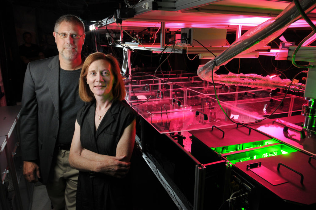 Physics professors Margaret Murnane and Henry Kapteyn of the Joint Institute for Laboratory Astrophysics (JILA) pose next to one of the laser apparatuses in their lab at the University of Colorado Boulder campus. Image Credit: Glenn Asakawa/University of Colorado)