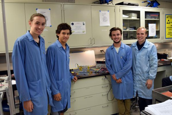 Pinterns (l-r) Everett Morton, Jacob Nelson, and Warren Fulton with aerospace PhD student Andrew Dahir in the CubeSat lab in front of a QB 50 test model. Image Credit: CU Boulder