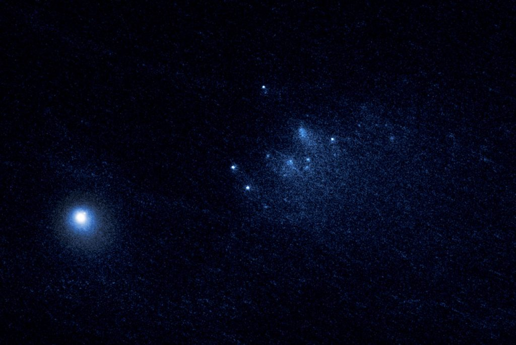 This NASA Hubble Space Telescope image reveals the ancient Comet 332P/Ikeya-Murakami disintegrating as it approaches the sun. The comet debris consists of a cluster of building-size chunks (center) that form a 3,000-mile-long trail. The fragments are drifting away from the comet. The main nucleus of Comet 332P is the bright object at lower left. This observation was made on Jan. 27, 2016, with Hubble's Wide Field Camera. Image Credit: NASA, ESA, D. Jewitt (UCLA)