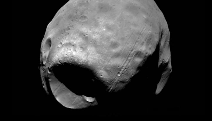 Lawrence Livermore National Laboratory researchers have demonstrated for the first time how an asteroid or comet could have caused the mega crater on Phobos without completely destroying the Martian moon. Image Credit: Viking Project, JPL, NASA