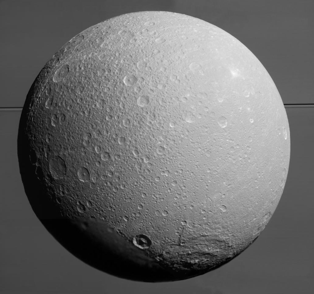 Dione with Saturn and its rings in the background. This image was taken by the Cassini spacecraft on 17 Augustus 2015. Image Credit: NASA/JPL-Caltech/Space Science Institute