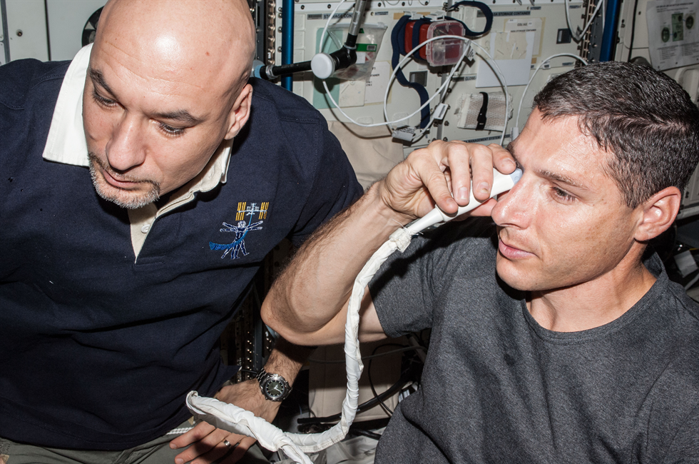 NASA astronaut Michael Hopkins, Expedition 37 flight engineer, performs ultrasound eye imaging in the Columbus laboratory of the International Space Station. ESA (European Space Agency) astronaut Luca Parmitano, flight engineer, assists Hopkins. Image Credit: NASA