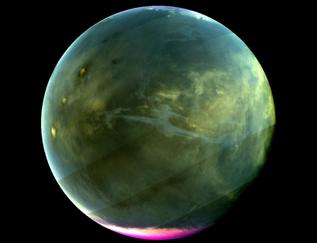 MAVEN's Imaging UltraViolet Spectrograph obtained this image of Mars on July 13, 2016, when the planet appeared nearly full when viewed from the highest altitudes in the MAVEN orbit. The ultraviolet colors of the planet have been rendered in false color, to show what we would see with ultraviolet-sensitive eyes. The ultraviolet (UV) view gives several new perspectives on Mars. Valles Marineris, a two-thousand-mile canyon system, appears prominently across the middle of the image as a blue gash. The deep canyon appears blue due to the scattering of ultraviolet light by the atmosphere, so strong that we cannot make out the bottom of the canyon. The greenish cast of the planet as a whole is a combination of the reflection of the surface plus the atmospheric scattering. The three tall Tharsis volcanoes appear near the left edge, dotted by white clouds forming as the winds flow over them. Bright white polar caps appear at both poles, typical for this season, in which there is a transition from southern-hemisphere winter to summer. The magenta-colored region visible at the south pole shows where ozone is absorbing ultraviolet light — the same property of ozone that protects life on Earth from harmful UV radiation. While ozone tends to be destroyed by chemical processes in the winter on Earth, different atmospheric chemistry at Mars caused it to build up in the winter there. A hint of ozone is also visible near the north pole; more will accumulate there as winter is coming. IUVS obtains images of Mars every orbit when the sunlit portion of the planet is visible from high altitude. Image Credit: NASA/Goddard/University of Colorado/LASP