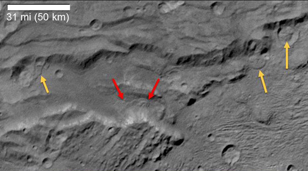 Scientists from NASA's New Horizons mission have spotted signs of long run-out landslides on Pluto's largest moon, Charon. This image of Charon's informally named Serenity Chasma was taken by New Horizons' Long Range Reconnaissance Imager (LORRI) on July 14, 2015, from a distance of 48,912 miles (78,717 kilometers). Arrows mark indications of landslide activity. Image Credit: NASA/JHUAPL/SwRI