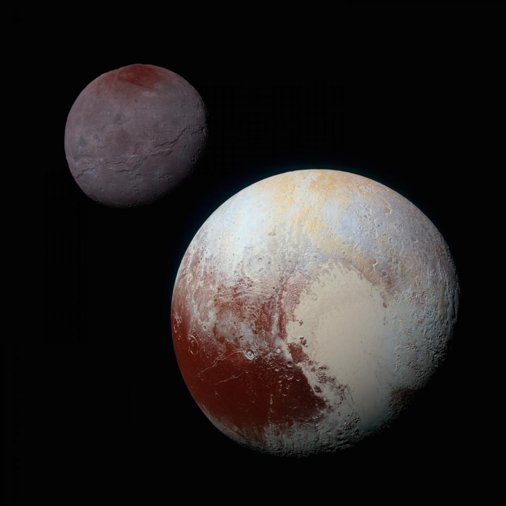 Pluto, shown here in the front of this false-color image, has a bright ice-covered 'heart.' The left, roughly oval lobe is the basin provisionally named Sputnik Planitia. Sputnik Planitia appears directly opposite Pluto's moon, Charon (back). Image Credit: NASA/JHUAPL/SWRI