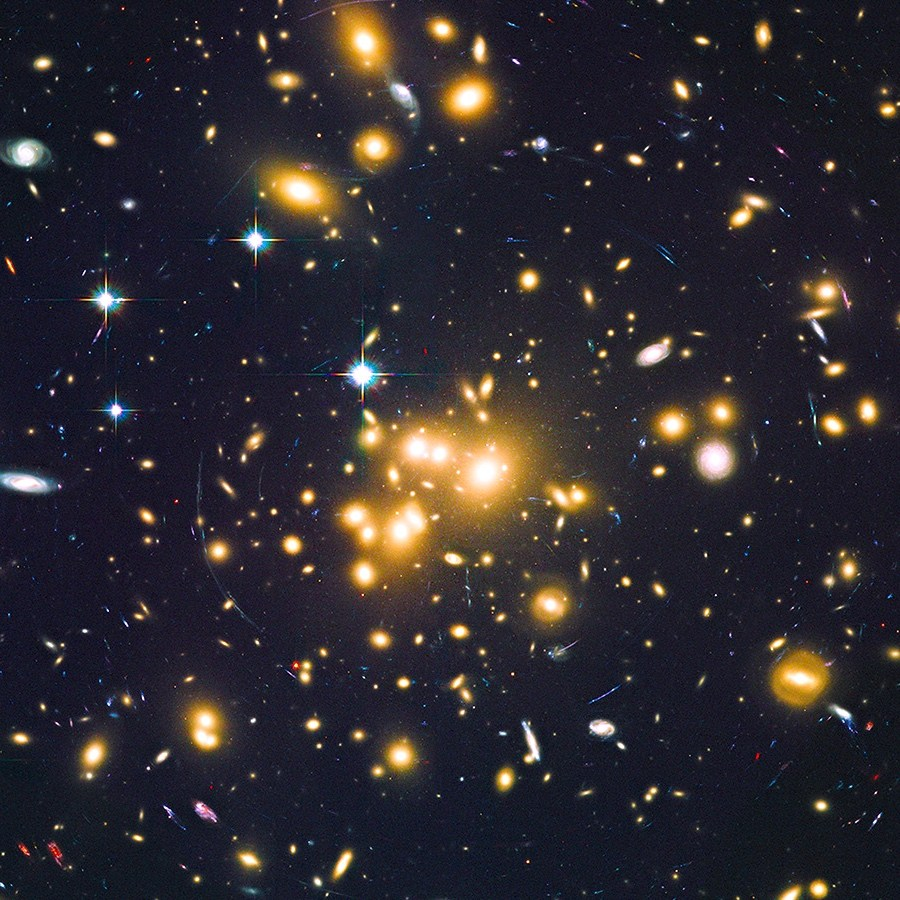 Massive cluster of galaxies Abell 1689 creates a strong gravitational effect on background and older galaxies, seen as arcs of light. Image Credit: NASA, ESA, B. SIANA, AND A. ALAVI