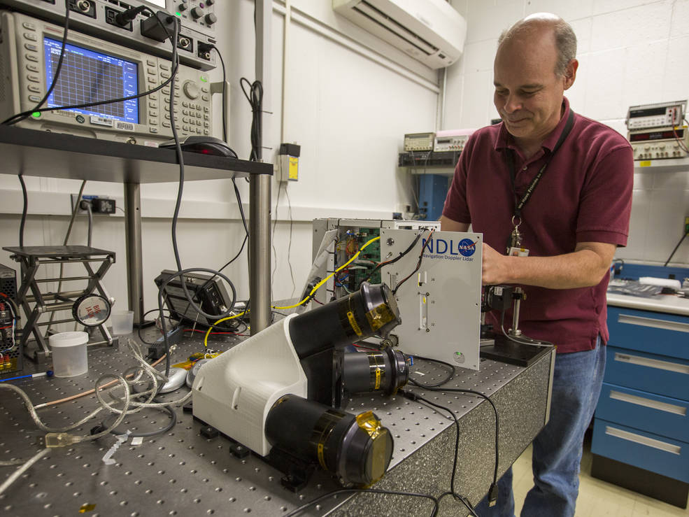 Bruce Barnes, who does electronics engineering and system integration for the Navigation Doppler Lidar, makes final preparations to the sensor in a lab at NASA's Langley Research Center. Image Credit: NASA/David C. Bowman