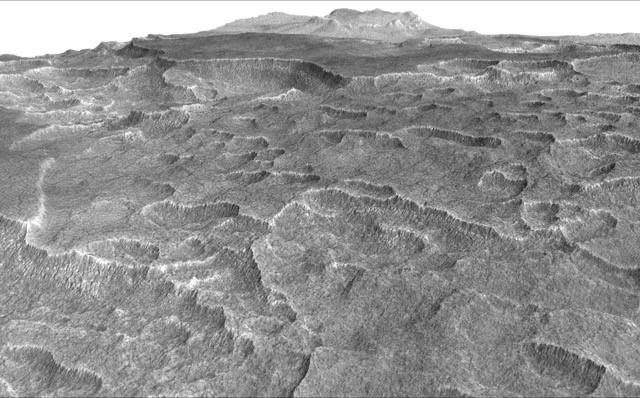 This vertically exaggerated view shows scalloped depressions in a part of Mars where such textures prompted researchers to check for buried ice, using ground-penetrating radar aboard NASA's Mars Reconnaissance Orbiter. They found about as much frozen water as the volume of Lake Superior. Image Credit: NASA/JPL-Caltech/Univ. of Arizona